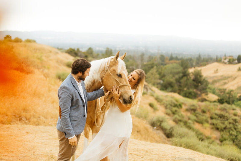 An engaged couple pet their horse on the hillside for this Granada Hills engagement photography session