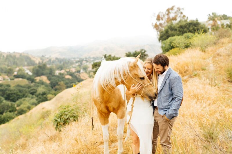 An engaged couple hold each other with their horse on the hillside for this Granada Hills engagement photography session