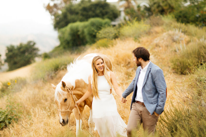 An engaged couple walk together with their horse on the hillside for this Granada Hills engagement photography session