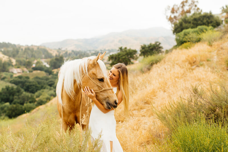 A woman pets her horse on the hillside for this Granada Hills engagement photography session