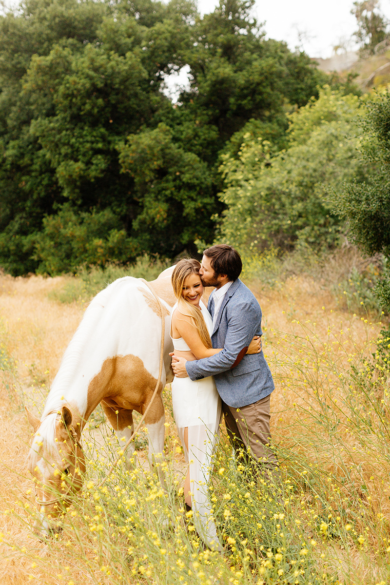 An engaged couple kiss holding each other with their horse on the hillside for this Granada Hills engagement photography session