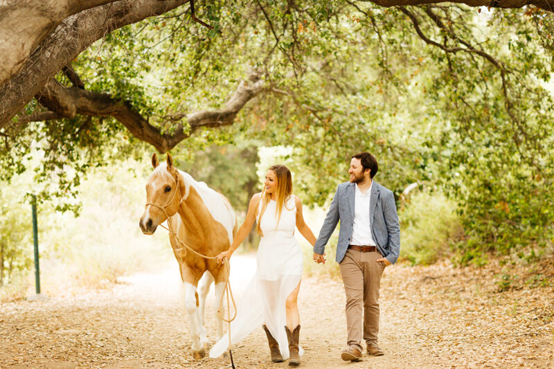An engaged couple walk together with their horse on a trail for this Granada Hills engagement photography session
