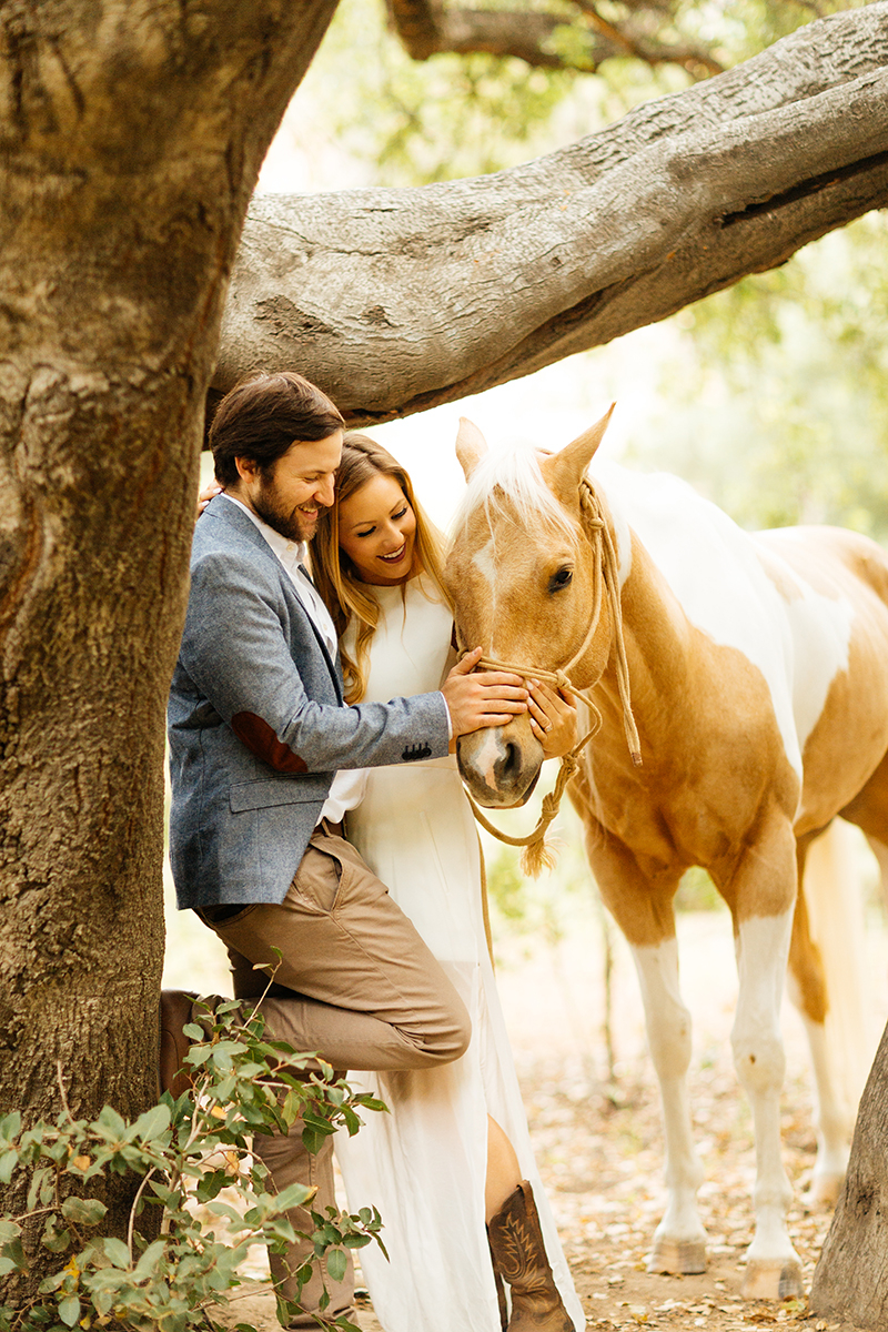 An engaged couple lean against a tree holding each other and petting their horse on a trail for this Granada Hills engagement photography session