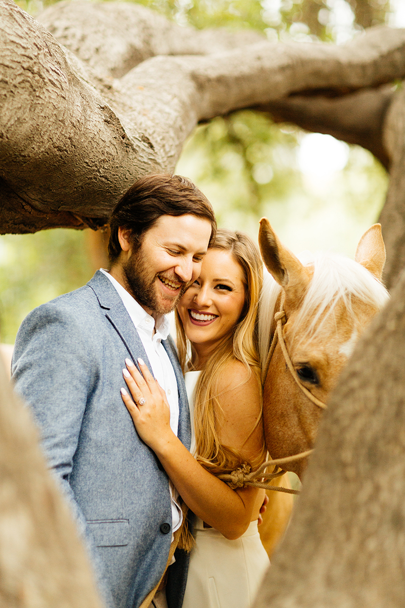 An engaged couple lean against a tree holding each other with their horse on a trail for this Granada Hills engagement photography session