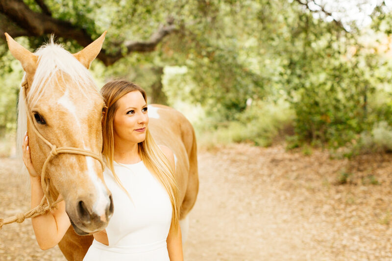 A woman stands next to her horse on a trail for this Granada Hills engagement photography session