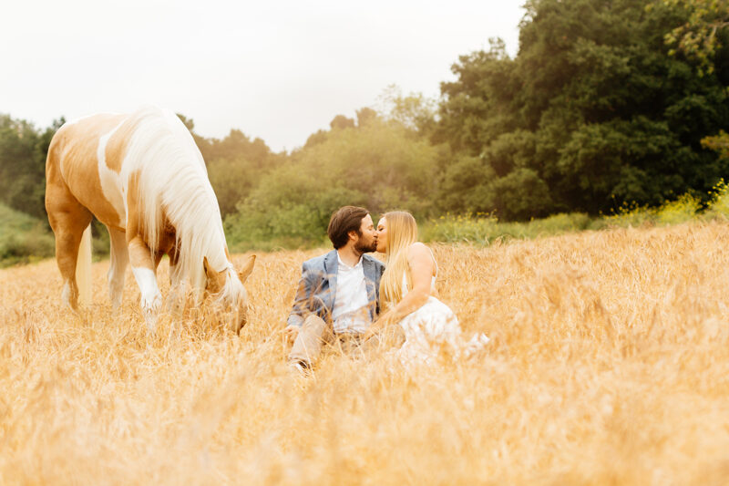 An engaged couple sit and kiss while holding each other with their horse grazing in a field for this Granada Hills engagement photography session