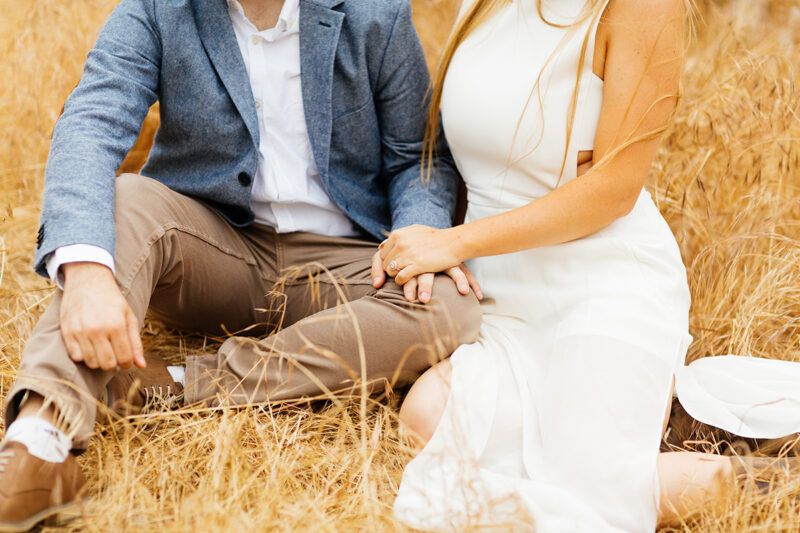 An engaged couple sit holding each other in a field for this Granada Hills engagement photography session