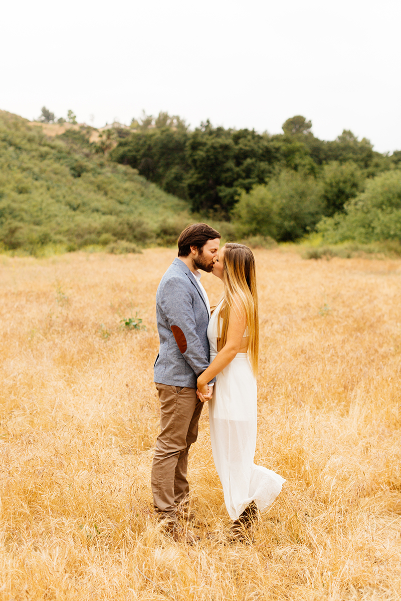 An engaged holding each other's hands kissing in a field for this Granada Hills engagement photography session
