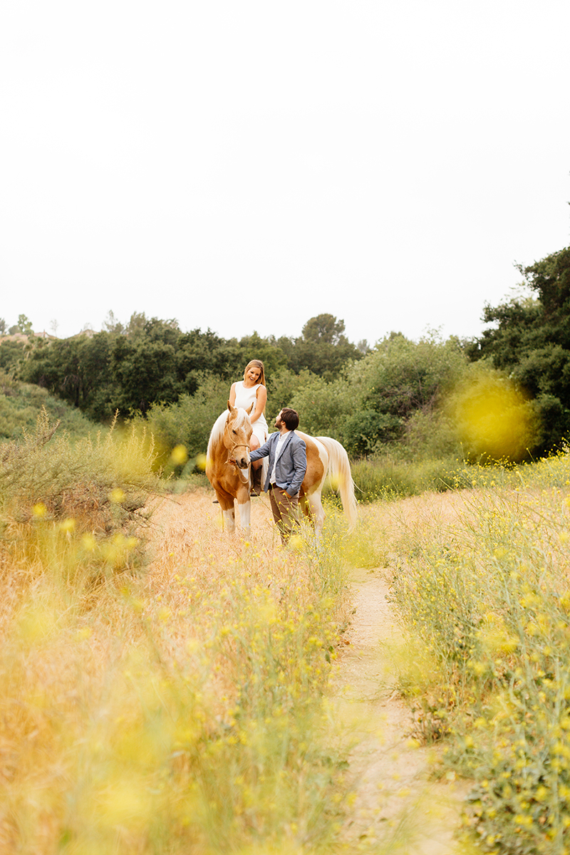An engaged couple smile at each other as she rides their horse in a field for this Granada Hills engagement photography session