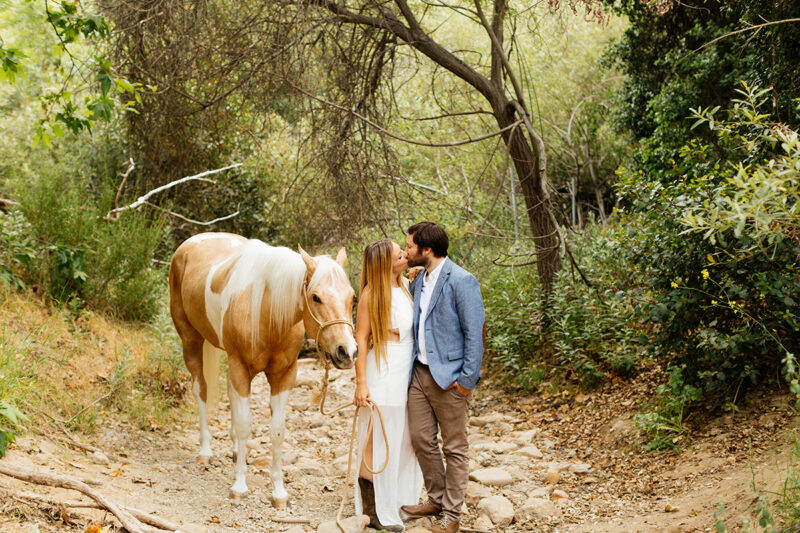 An engaged couple kiss holding each other with their horse on a trail for this Granada Hills engagement photography session
