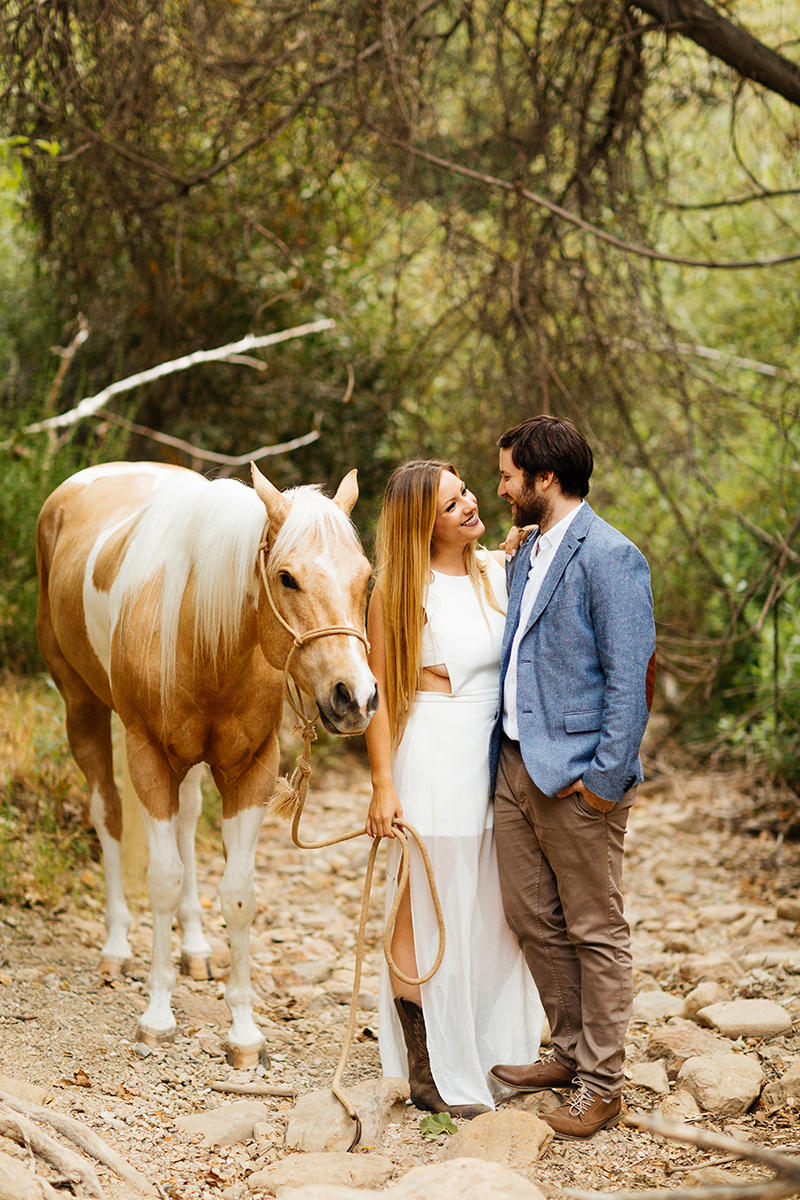 An engaged couple hold each other with their horse on a trail for this Granada Hills engagement photography session