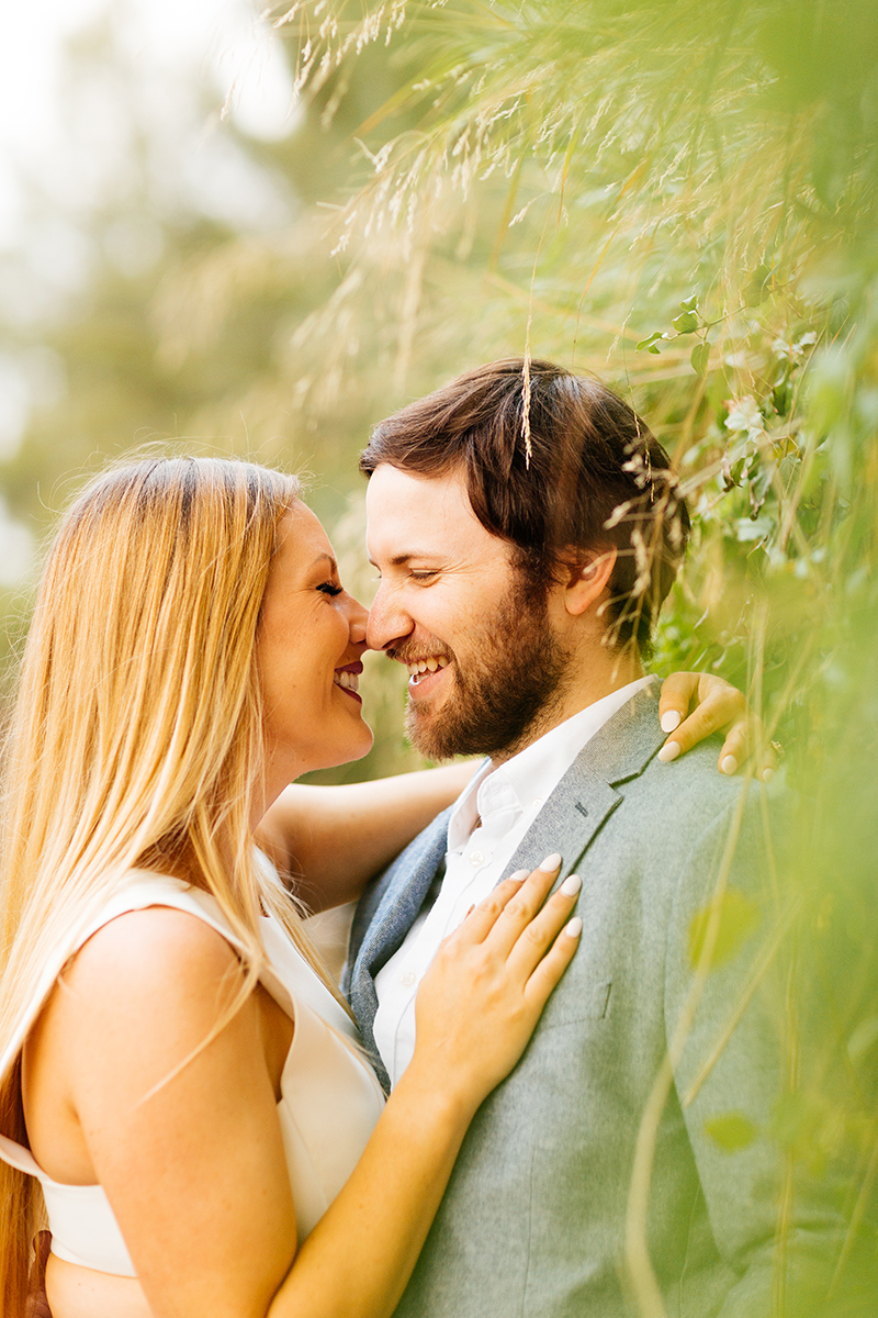 An engaged couple hold each other close leaning on a wall covered in plants for this Granada Hills engagement photography session