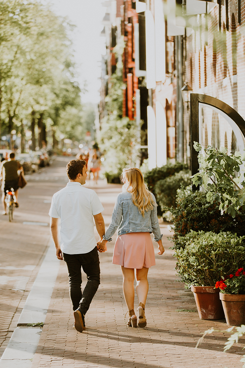 A couple hold hands and walk together through a neighborhood next to a canal for this Amsterdam couples photography session