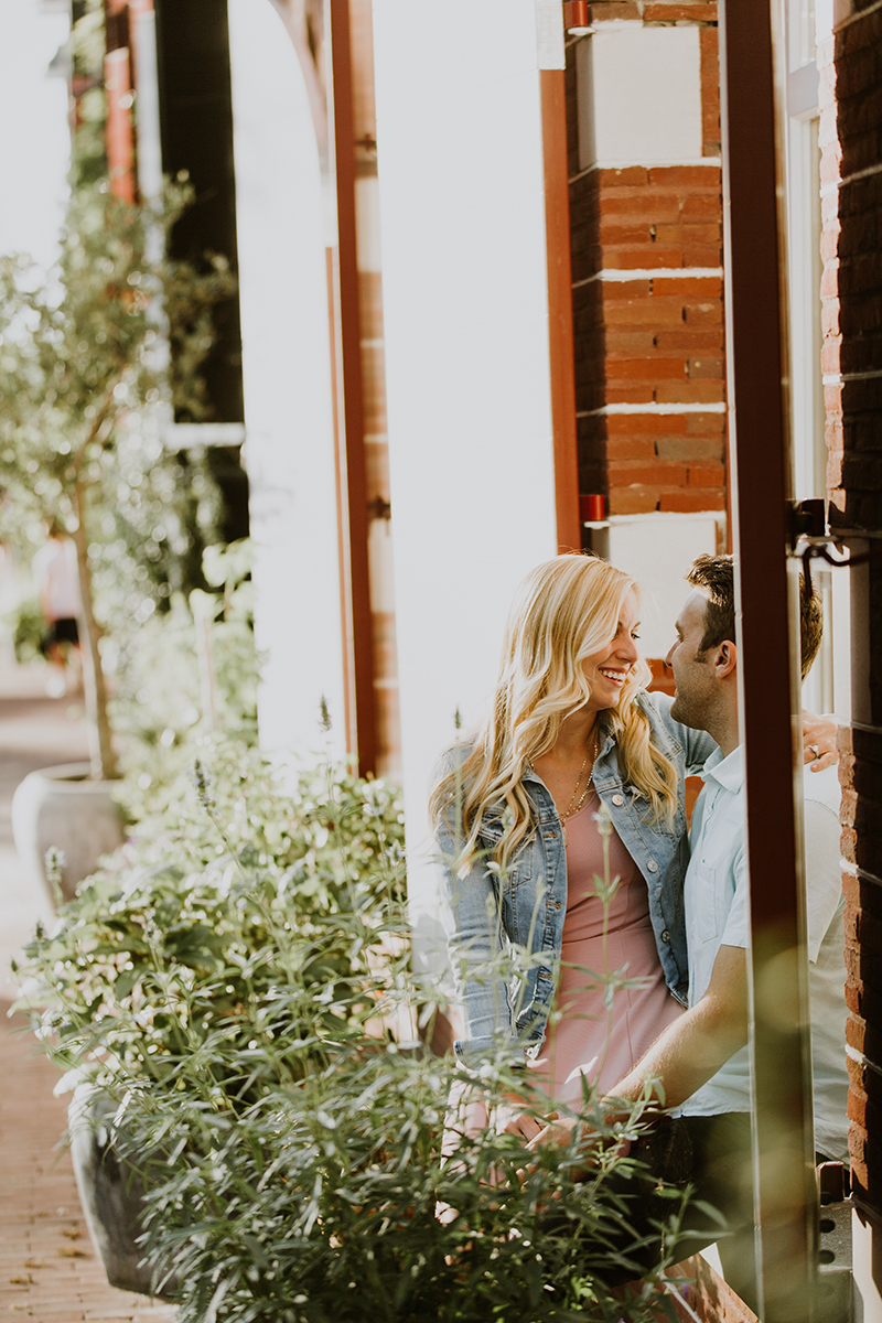 A couple sit together in a window holding one another in a neighborhood next to a canal for this Amsterdam couples photography session