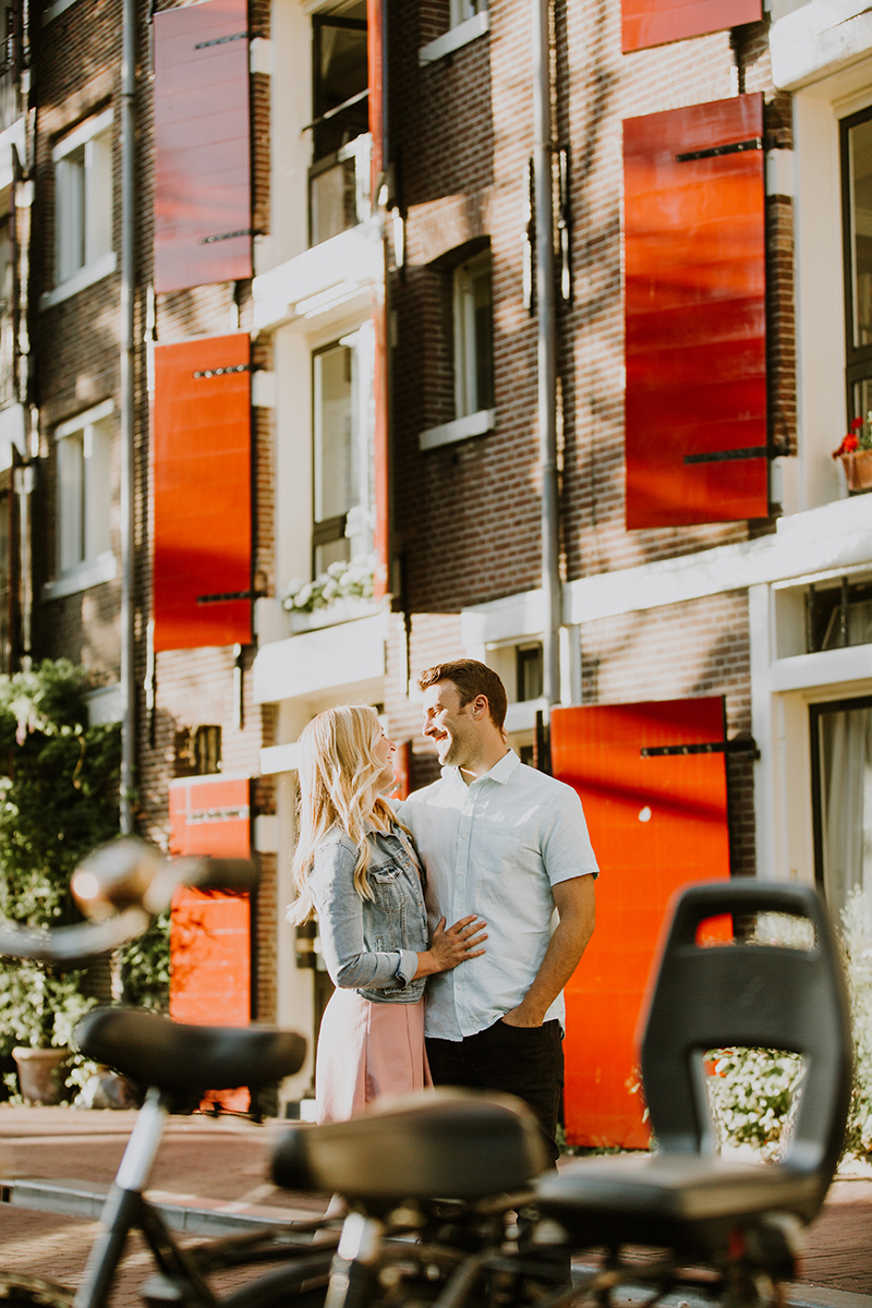 A couple hold one another close in a cute neighborhood next to a canal for this Amsterdam couples photography session