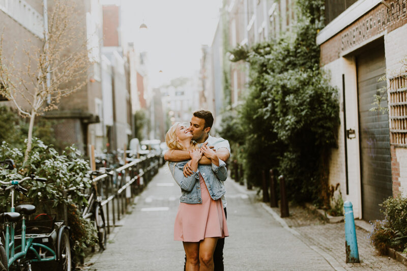 A couple hold one another close in a cute neighborhood for this Amsterdam couples photography session