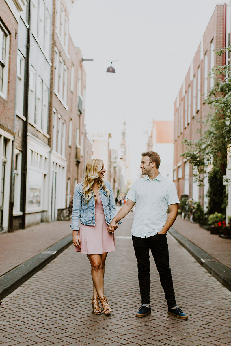 A couple hold each other's hands and walk in a cute neighborhood for this Amsterdam couples photography session