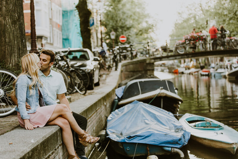 A couple sit together and kiss on the edge of a canal for this Amsterdam couples photography session