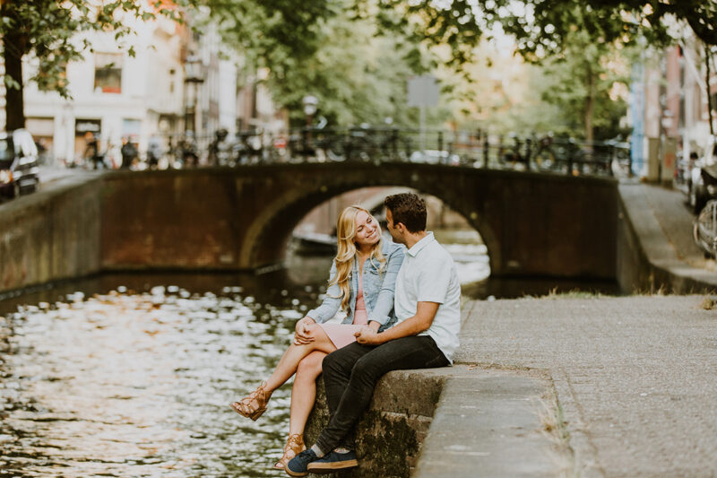 A couple sit together on the edge of a canal for this Amsterdam couples photography session