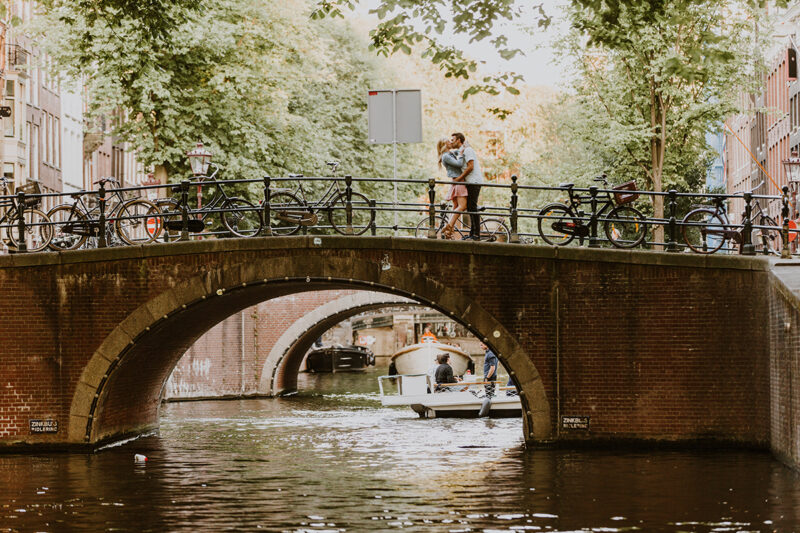 A couple hold one another close and kiss on a bridge over a canal for this Amsterdam couples photography session