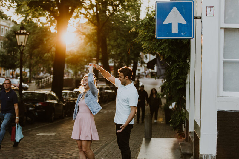 A couple dance next to a canal at sunset for this Amsterdam couples photography session