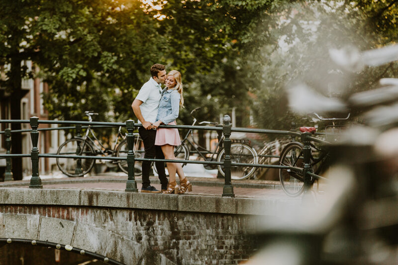 A couple hold one another close on a bridge over a canal for this Amsterdam couples photography session