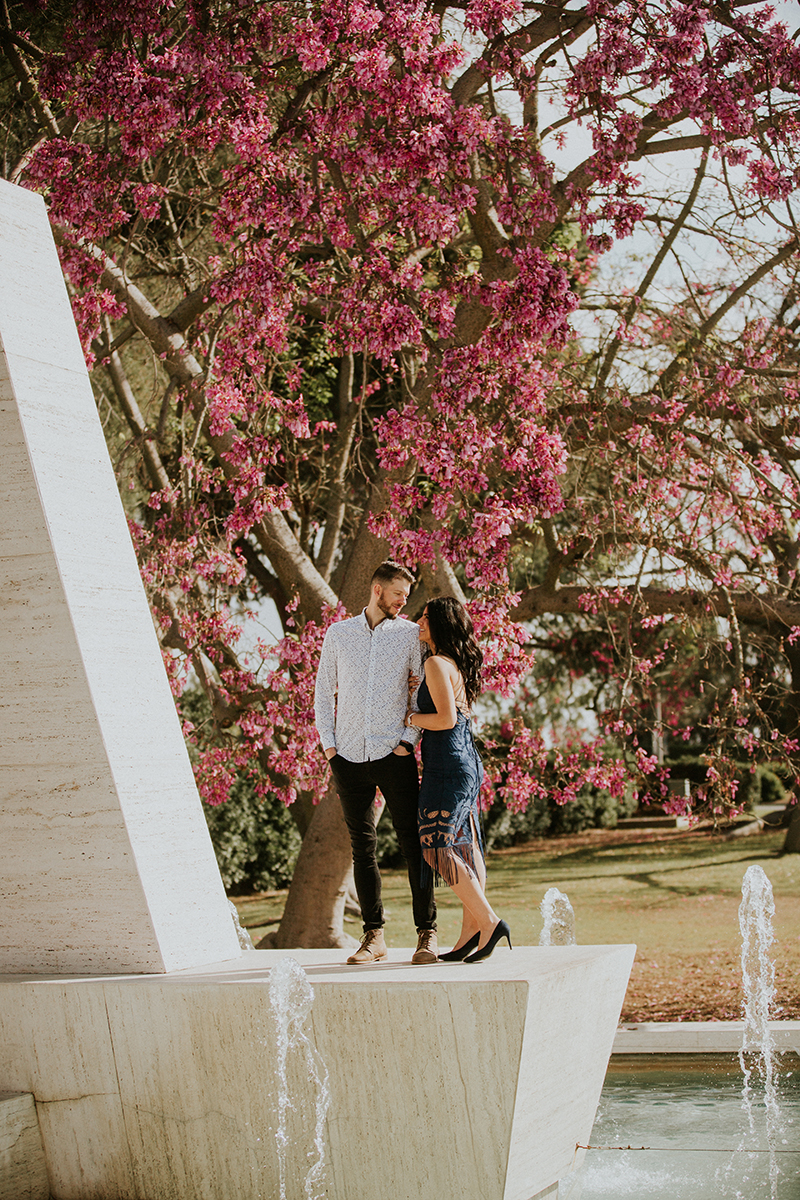 A couple hold each other under pink cherry blossoms at the Los Angeles County Arboretum and Botanic Garden for this Los Angeles engagement photography session