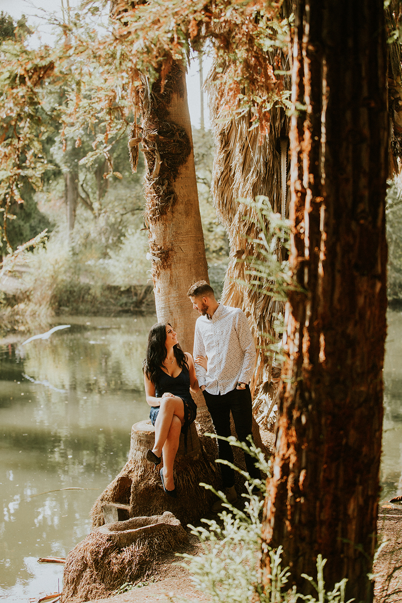 A couple hold each other in a forest near water at the Los Angeles County Arboretum and Botanic Garden for this Los Angeles engagement photography session