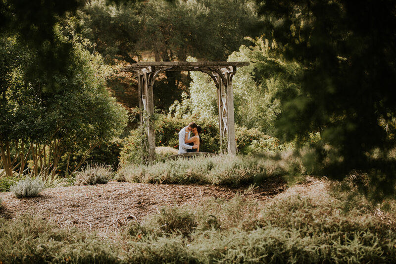 A couple hold each other and kiss at an arch at the Los Angeles County Arboretum and Botanic Garden for this Los Angeles engagement photography session