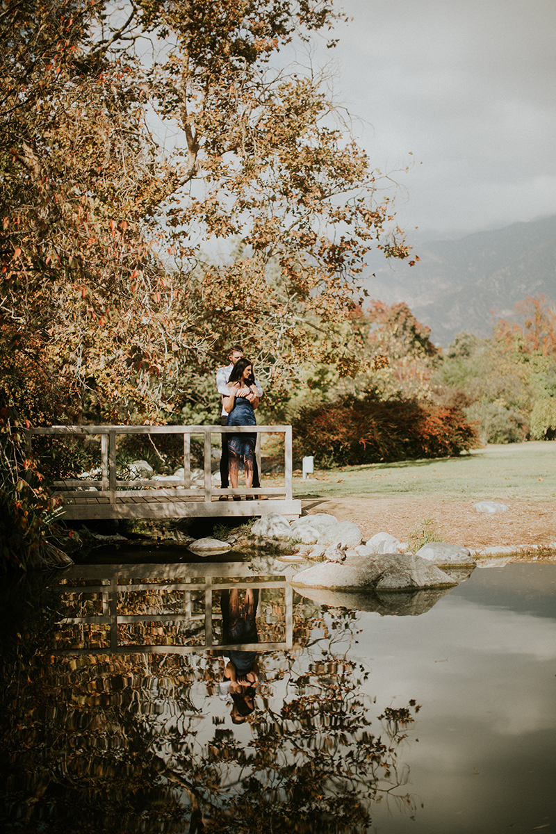 A couple hold each other on a bridge at the Los Angeles County Arboretum and Botanic Garden for this Los Angeles engagement photography session