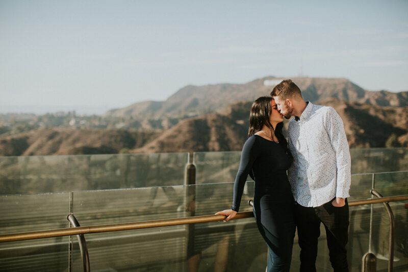 A couple hold each other and kiss at the Los Angeles Observatory for this Los Angeles engagement photography session