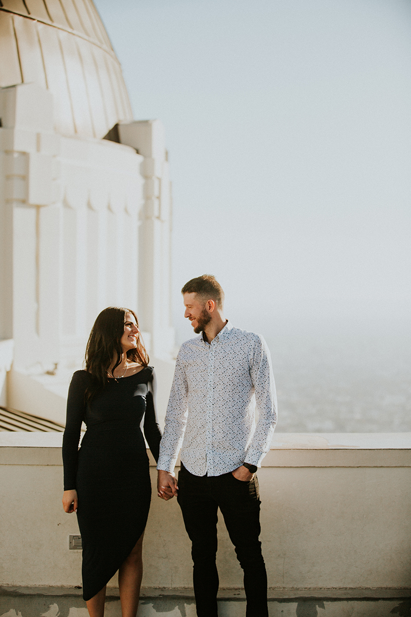 A couple hold each other's hands at the Los Angeles Observatory for this Los Angeles engagement photography session
