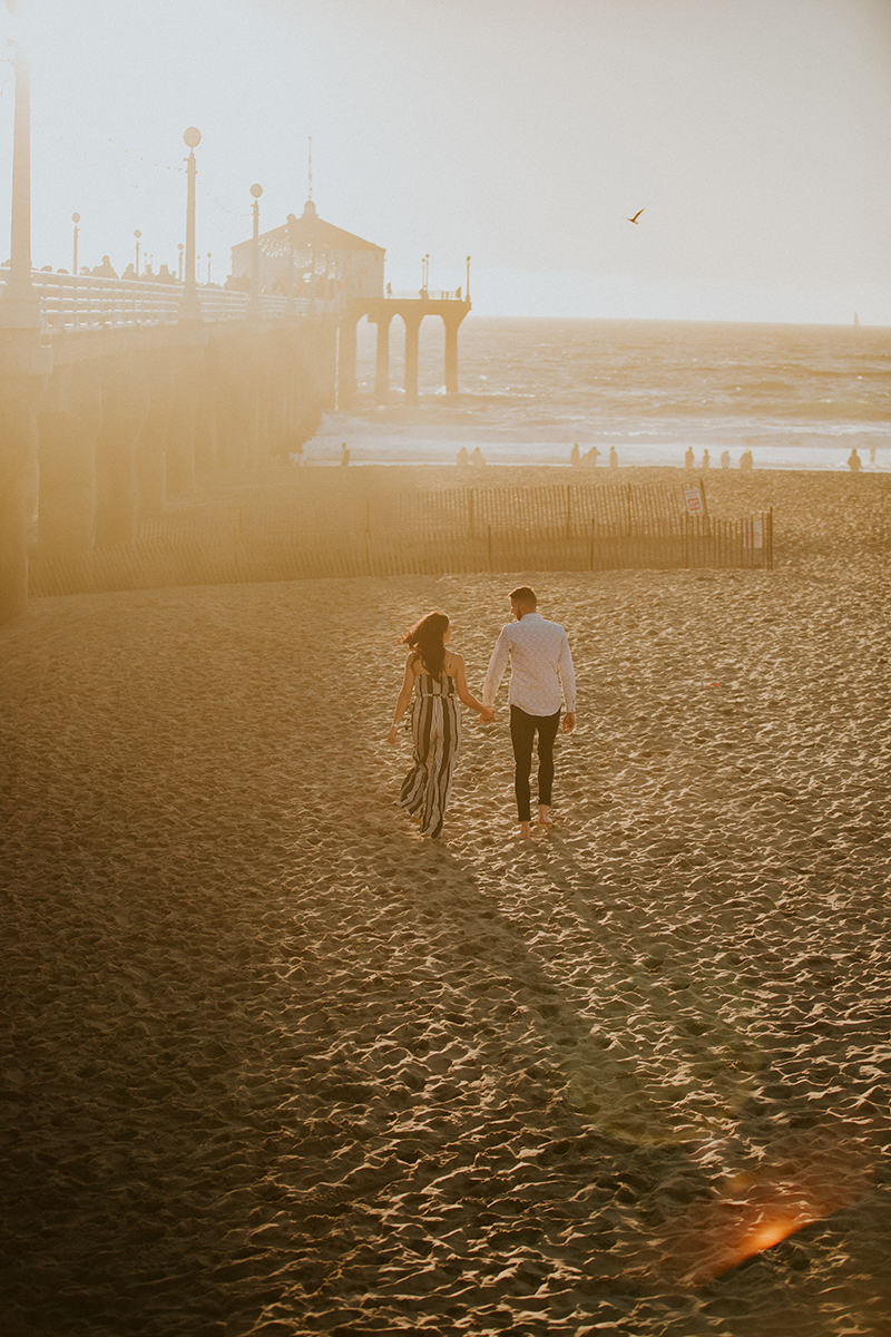 A couple walk together at sunset on the beach near the Santa Monica Pier for this Los Angeles engagement photography session