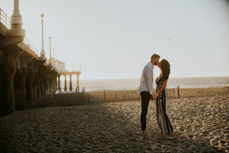 A couple kiss at sunset on the beach near the Santa Monica Pier for this Los Angeles engagement photography session