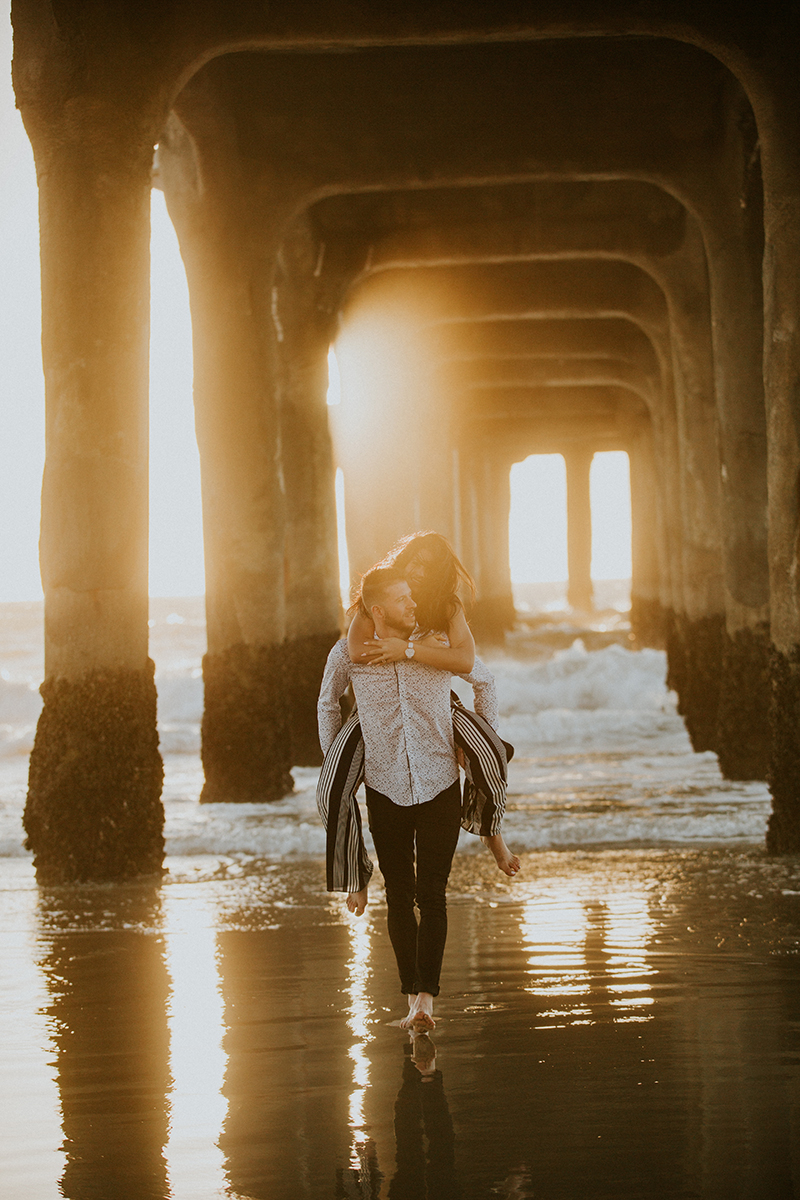 A couple walk together as he gives he a piggyback ride at sunset on the beach under a pier near the Santa Monica Pier for this Los Angeles engagement photography session