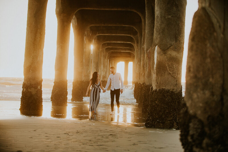 A couple walk together at sunset on the beach under a pier near the Santa Monica Pier for this Los Angeles engagement photography session