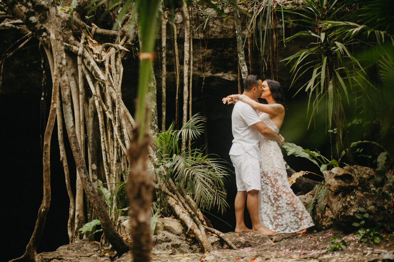 A couple hold one another kissing in front of a cenote in Mexico wearing a beautiful white dress and white shorts with a shirt for a Cenote Azul engagement photography session