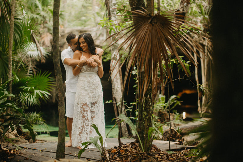 A couple hold one another smiling in front of a cenote in Mexico wearing a beautiful white dress and white shorts with a shirt for a Cenote Azul engagement photography session