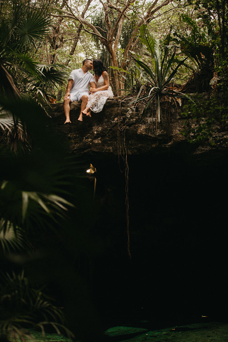 A couple sit next to each other kissing on top of a cenote in Mexico wearing a beautiful white dress and white shorts with a shirt for a Cenote Azul engagement photography session