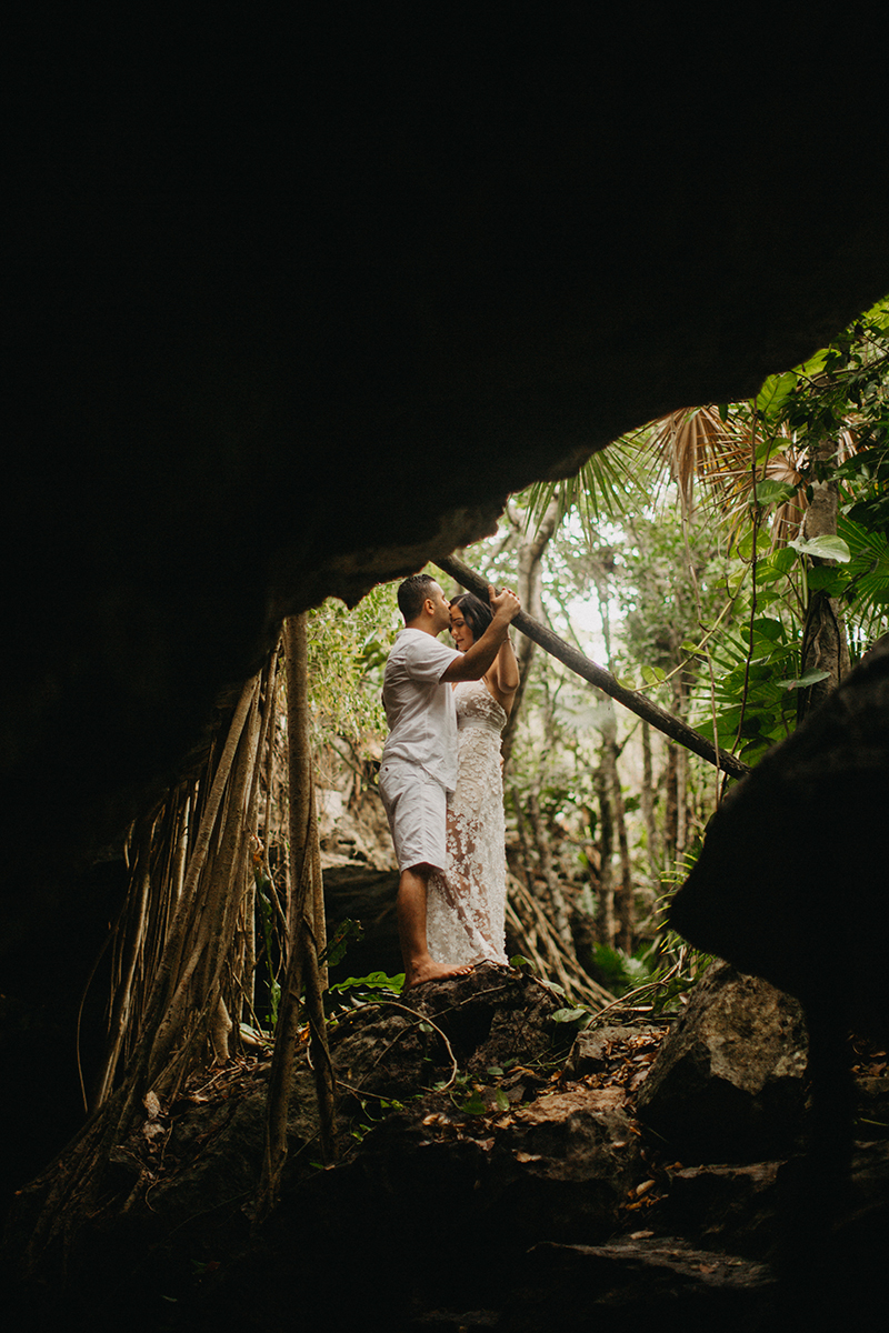A couple together kissing at the edge of a cenote in Mexico wearing a beautiful white dress and white shorts with a shirt for a Cenote Azul engagement photography session