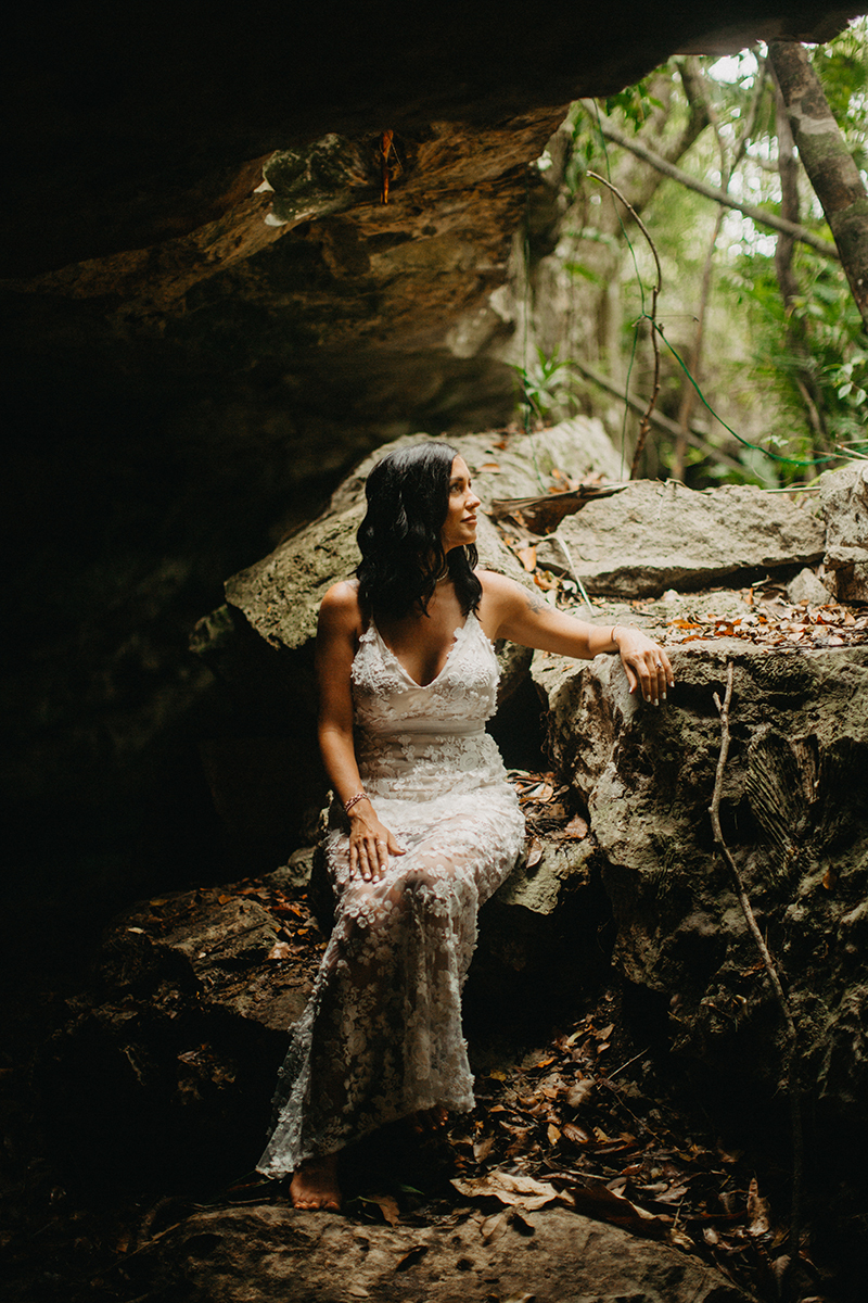 A woman poses sitting inside of a cenote in Mexico wearing a beautiful white dress and white shorts with a shirt for a Cenote Azul engagement photography session