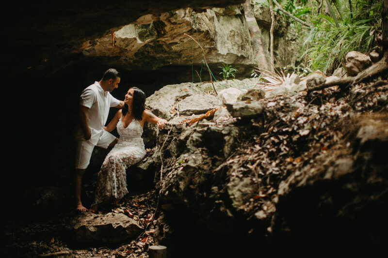 A couple together inside of a cenote in Mexico wearing a beautiful white dress and white shorts with a shirt for a Cenote Azul engagement photography session
