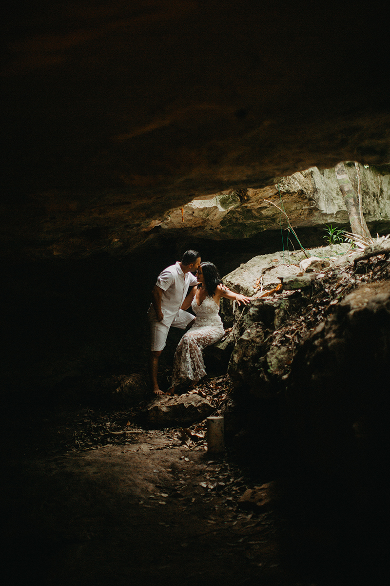 A couple together kissing inside of a cenote in Mexico wearing a beautiful white dress and white shorts with a shirt for a Cenote Azul engagement photography session