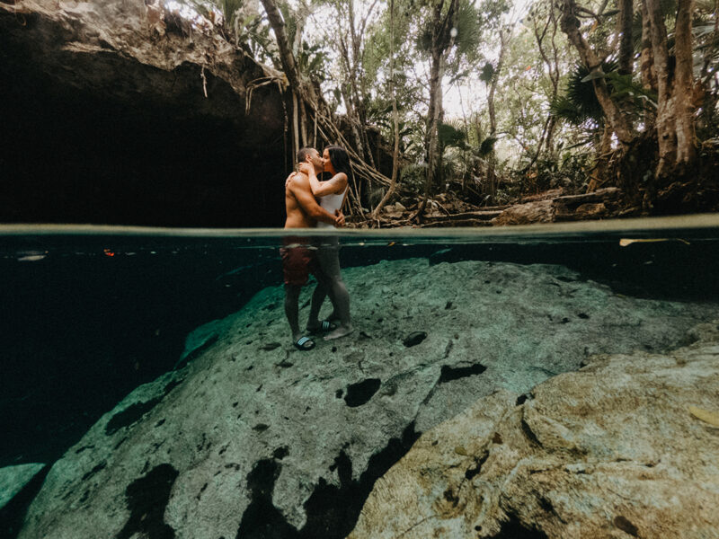 A couple stand together kissing in the water of a cenote in Mexico wearing a white swimsuit and orange shorts for a Cenote Azul engagement photography session