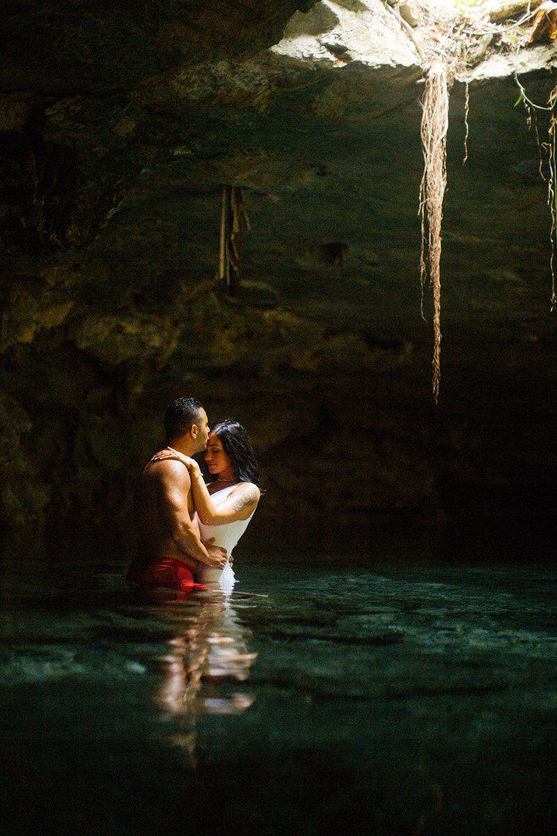 A couple stand together in the water of a cenote in Mexico wearing a white swimsuit and orange shorts for a Cenote Azul engagement photography session