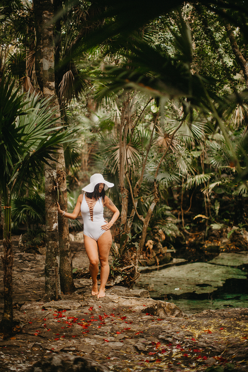 A beautiful woman poses near a cenote in Mexico wearing a white swimsuit and a beach hat for a Cenote Azul engagement photography sessionA beautiful woman poses near a cenote in Mexico wearing a white swimsuit and a beach hat for a Cenote Azul engagement photography session