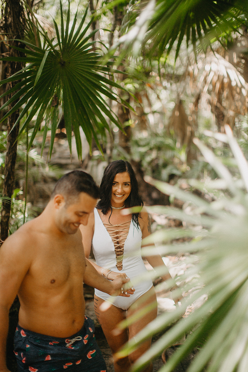 A couple walk together through the jungle near a cenote in Mexico wearing a white swimsuit and orange shorts for a Cenote Azul engagement photography session