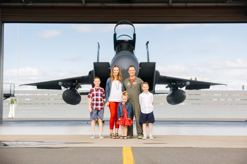 A family stands holding each other close in front of an F-15 at Barnes Air National Guard Base wearing a flight suit and coordinated outfits for these F-15 fighter pilot family photos