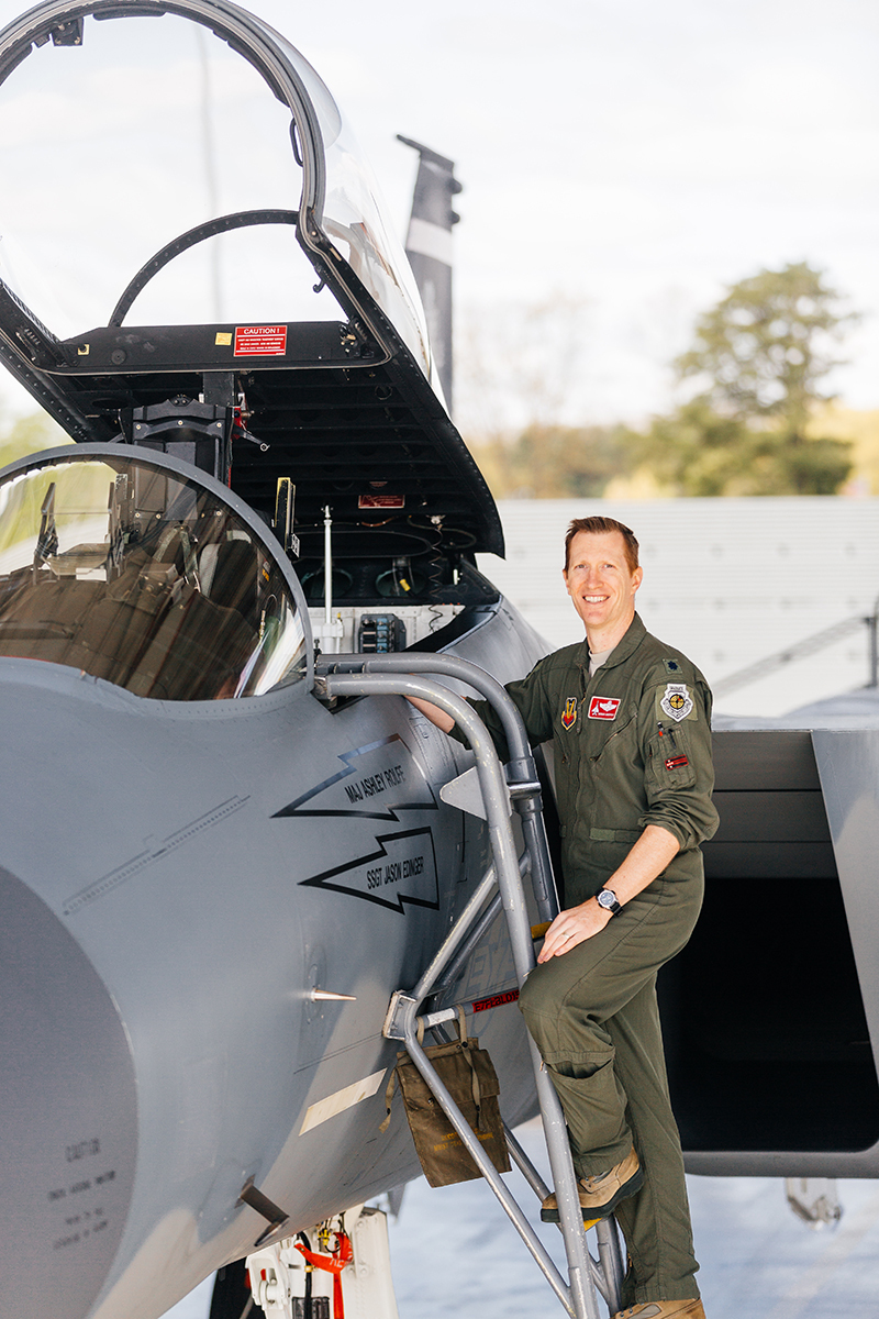 A pilot stands on a ladder up to an F-15 at Barnes Air National Guard Base wearing a flight suit for these F-15 fighter pilot family photos
