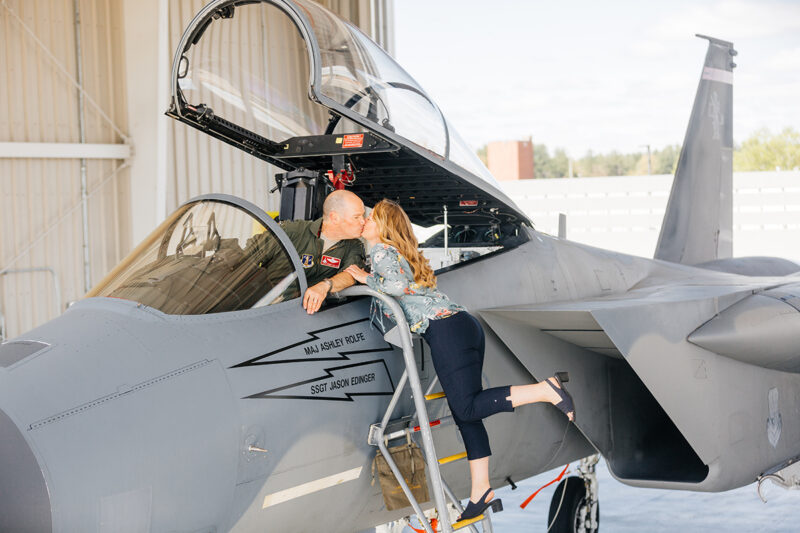 A pilot sits in the cockpit of an F-15 with his wife on a ladder kissing him at Barnes Air National Guard Base wearing a flight suit and a coordinated outfit for these F-15 fighter pilot family photos